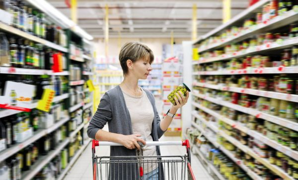 pretty woman with a cart shopping and choosing goods at the supermarket; Shutterstock ID 160898930; PO: aol; Job: production; Client: drone