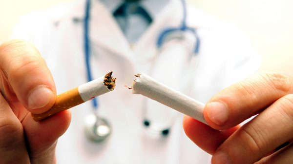 doctor breaking apart a cigarette - concept for stop smoking