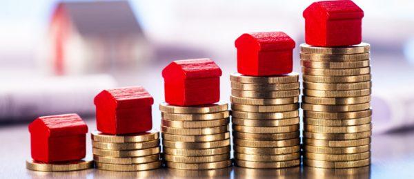 Kleine rote Häuser stehen auf Stapeln aus Münzen mit Bauplänen und einem Architekturmodell im Hintergrund.