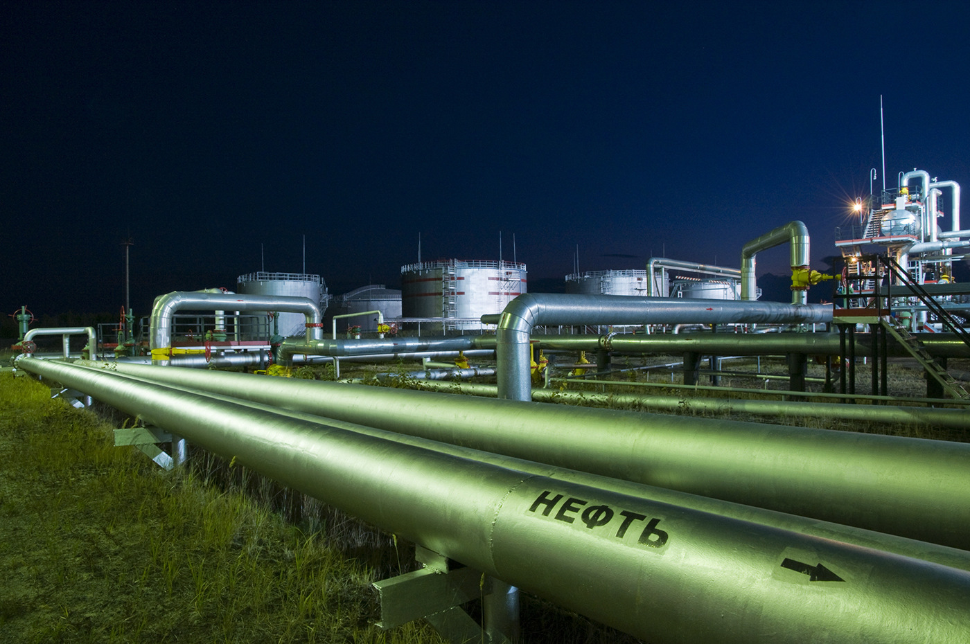 """Pipelines on the background of a processing plant. On the tube, it is written in Russian the word """"oil."""" At night, the different light sources are concentrated in different parts of the plant, creating different shades of color refinery."""